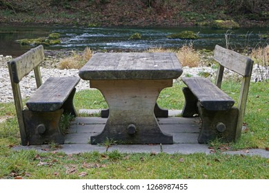 An old pic-nic place with wooden benches and tables with the Doubs river in the back (Goumois, Jura)