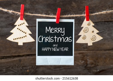 Old pictures on wood background with Christmas decoration.Wooden christmas tree hanging with old picture on rope ant lettering Marry Christmas and Happy new year