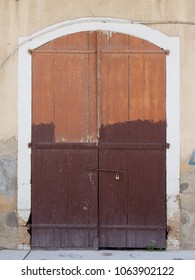 old picturesque decaying half brown painted wooden double doors bolted shut with a padlock set in a white stone frame in a faded pink concrete wall on a street