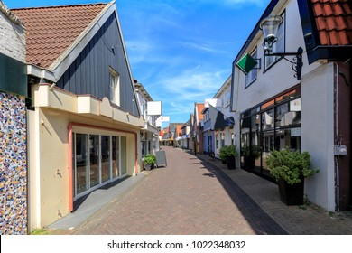 Old and picturesque houses, buildings and architecture typical on a shopping street downtown Den Burg on the wadden island Texel on a sunny day in Summer