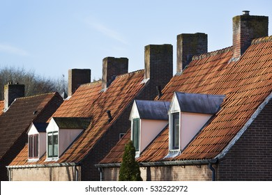 Old picturesque red tiled roofs with dormers and chimneys in the Netherlands