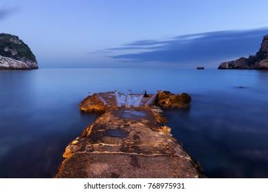 Old Pier on Mediterranean Sea at dusk.