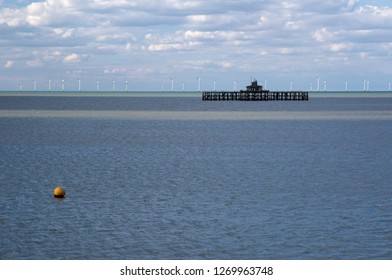 Old pier with row of wind turbines off shore