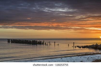Old pier at sunrise, sandy beach of the Baltic Sea, Latvia, Europe