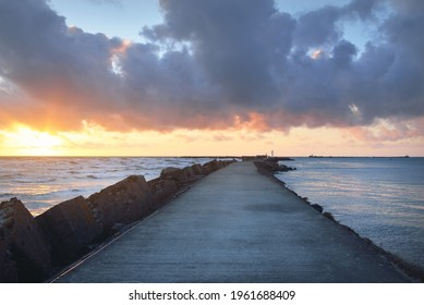 Old pier (walkway, promenade) to the lighthouse. Breakwaters close-up. Clear blue sky, pink sunset clouds, golden sunlight. Seascape, cloudscape. Baltic sea. Spring. Tourism, landmark, navigation