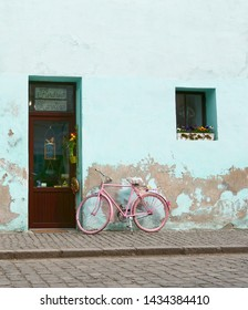 Old pink bicycle leaning against a green damaged exterior wall on the sidewalk near a door.