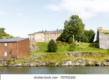 Old pinkish mansion behind water on top of a hill in Suomenlinna, Finland