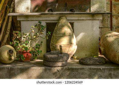 Old pitchers,stone millstones and a flower pot at the foot of an old barbecue oven at the stone wall in a rural courtyard