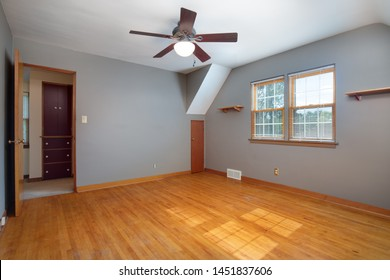 An old, plain grey room with no furniture and hardwood floors looking towards the hallway.
