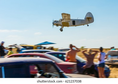 The old plane flies low over people and creates a futile situation at the air show.