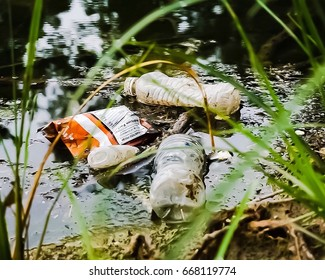 Old plastic bottles and bags littering a pond