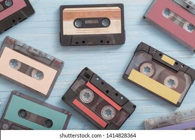 Old plastic cassette on blue wooden background. Retro music concept