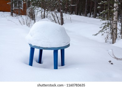 Old plastic table in yard under thick layer of snow after snowfall at winter day