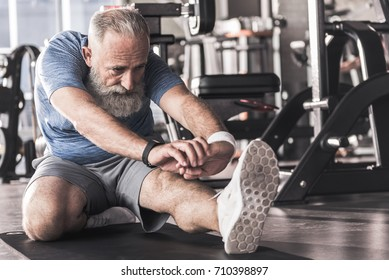 Old pleasant male is concentrated on his exercises
