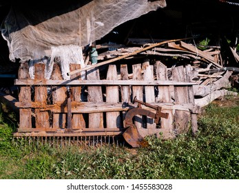 Old plowing equipment used rusted agricultural farming equipment in shape of small plow left  in front of wooden boards wall