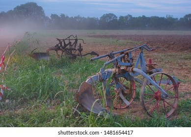 Old plows for tractors for working in the field, which were produced since 1934. The field is very dusty in the evening, as some tractors demonstrate their work in the field. Ferragosto, Italy