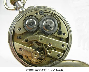 Old pocket fob watch mechanism with brass metal silver and gold mechanical parts.