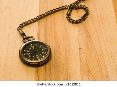 An old pocket watch with a chain, shot on a wooden table