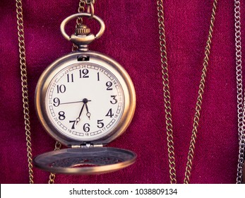 old pocket watch and chains on the red floor