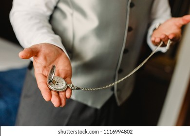 Old pocket watch in the hands of a man