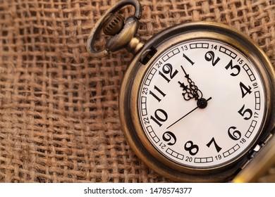 Old pocket watch on burlap background