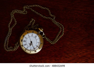 Old pocket watch on a wooden table.