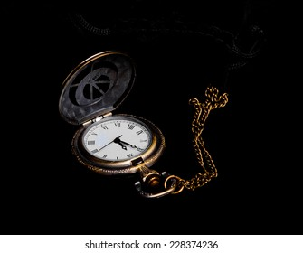 Old pocket watch showing near-New Year over black background