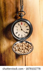 Old pocketwatch with hemp seeds on a wooden wall. Close up.