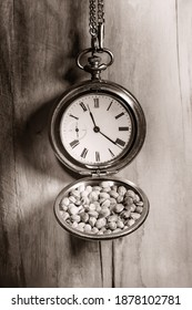 Old pocketwatch with hemp seeds on a wooden wall. Close up. Black white.