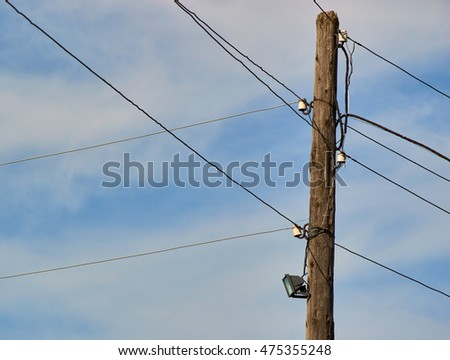 old pole with lamp and wires  sky and clouds