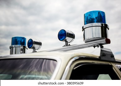 Old police car round domed rotating blue emergency lights on a 1960s police car