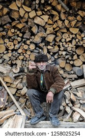 Old poor man sit and smokes a cigarette in front of woods cut for winter