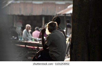 An old poor man smoking a cigarette in a public place unique photograph