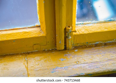 Old, poorly painted yellow window frames with flaking off paint and vintage aluminum bolt. Macro closeup shot.