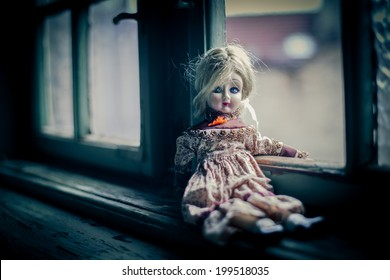 Old porcelain doll at the window