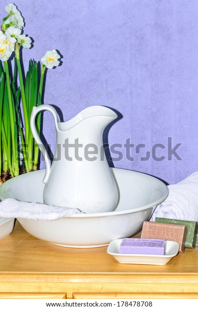 Old porcelain water can with natural soap and white towel