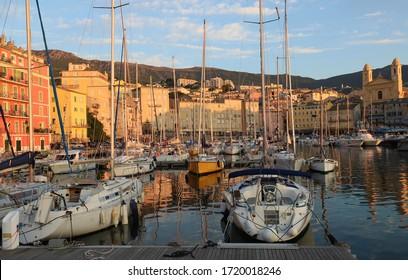 Le vieux port de Bastia Corsica France avec l'église historique Saint-Jean-Baptiste et les boutiques restaurants cafés et yachts bateaux dans le port avec condos et bâtiments médiévaux