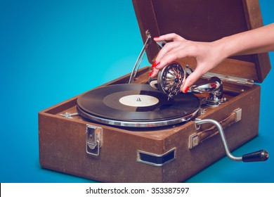 Old portable gramophone with female hand pin-up styled isolated, on blue background with empty space