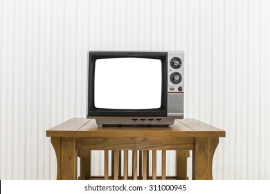 Old portable television with antenna on wood table with cut out screen and clipping path.