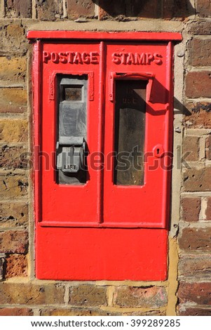 An Old Postage Stamp Dispenser Machine In A Red Brick Wall
