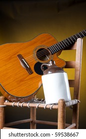 An old potter ceramic country jug with a guitar and rope bottom chair on a gold background in  the  vertical format with copy space.