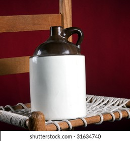 An old pottery ceramic country jug and rope bottom chair on a red background in the square format.