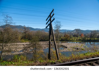 Old power line support near the river and mountains.