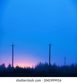 Old power line supports in rural areas. Night, fog. Electric poles in the mist, Russian countryside.