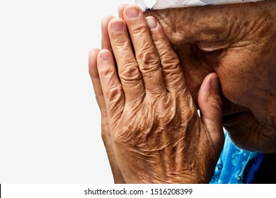 Old praying grandmother. Mother knelt in prayer for the children. Close-up of a praying woman face. Tearful prayer to God