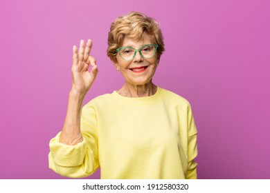 old pretty woman feeling successful and satisfied, smiling with mouth wide open, making okay sign with hand