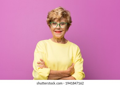 old pretty woman laughing happily with arms crossed, with a relaxed, positive and satisfied pose