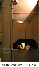 old priest inside the confessional in a Christian church waiting for the faithful to confess