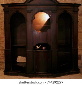 old priest inside the wooden confessional in a Christian church waiting for the faithful to confess