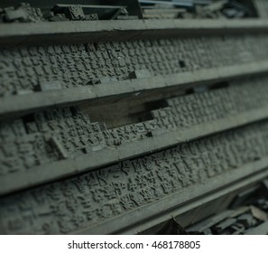 Old printing press letter blocks in a wooden shelf.